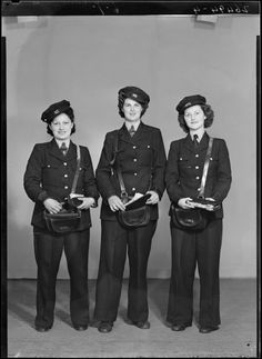 Studio portrait of three unidentified women tram conductors in uniform with leather ticket pouches, probably taken during World War II by S P Andrew Ltd.
