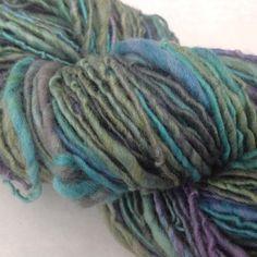 50% Seide 50% Wolle handgesponnen und -gefärbt als Singlegarn 109 g /LL 160,2m  Dieses Garn erhält seine faszinierende Ausstrahlung duch die Kombination von lebhaften Türkis mit Lila und Grün....
