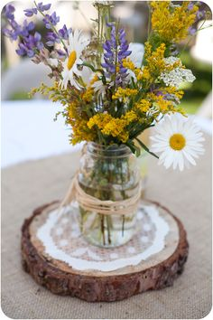 Wildflowers in a mason jar on a doily a top a slice of tree.