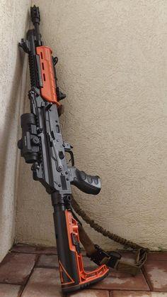 Custom AK with orange Magpul furniture.