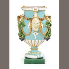 A massive Minton majolica vase, dated 1877  Of urn shape applied with satyr's masks alternating with bunches of hanging grapes garlanded by rope, set against a turquoise ground with a light purple interior, resting upon a dark green square base, 95.5cm high, impressed MINTONS and date cipher for 1877