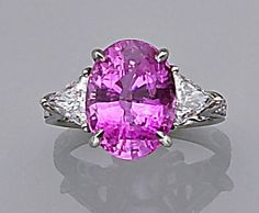A pink sapphire and diamond ring  centering an oval-shaped pink sapphire weighing 6.24 carats, flanked by triangle-shaped diamonds, completed by round brilliant-cut diamond-set mount; estimated total diamond weight: 1.00 carat; mounted in platinum.