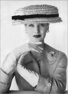 Sunny Harnett is wearing a rough gold straw hat with giant brim and black grosgrain band by Adolfo of Emme, Indian raw silk suit by Marquise, diamond brooch by Van Cleef & Arpels, photo by Karen Radkai, Vogue, January 1956