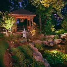 parterre de fleurs avec galets, pergola en bois, petite lanterne en pierre zen, arbres verts, déco exterieur jardin