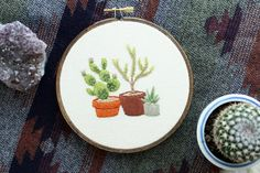 ***MADE TO ORDER***  Please allow 1-2 weeks for your embroidery to be created - depending on my work load (if you need it sooner please message me) Im a one woman show so please be patient with me  No green thumb? No worries! Heres a few plants youll never have to fool with, just hang it up and admire! A cute trio of plants in containers. OPTIONS: - Hoop Color: Natural/Unstained, Golden Caramel or Dark Walnut - Fabric Color: Natural/Ivory, Indigo or Black DETAILS: - Hand-drawn and ...