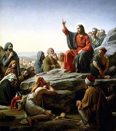 Jesus sits atop a mount, preaching to a crowd