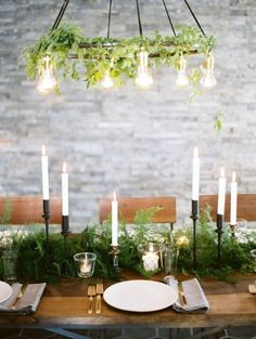 A leaf and vine covered chandelier and green centerpieces with candles for a rustic wedding.