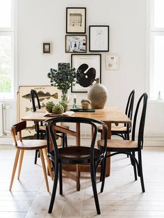 Beautiful dining area with a large wooden table, different chairs in black and brown and a small art gallery.