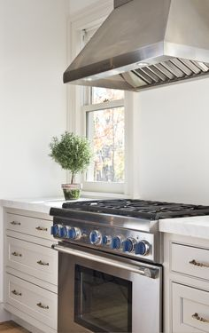kitchen renovation details: thick Carrara marble counters, Thermador range and windows that go down to the counters give the kitchen a more historic look