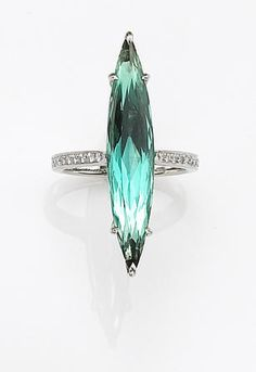 A tourmaline and diamond ring, Nardi, centering an elongated marquise-cut greenish blue tourmaline, weighing 6.92 carats, measuring approximately 33.50 x 6.40 x 5.30mm., completed by round brilliant-cut diamond shoulders; unsigned, attributed to Nardi; mounted in platinum.
