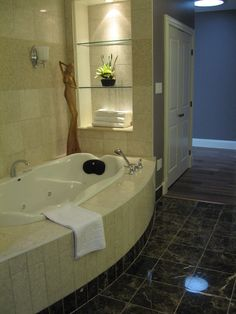 Custom designed bath with marble walls and shelving.