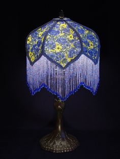 This lamp, with a hand beaded fire polished Czech glass fringe has a beautiful  fabric of blue and yellow flowers and blue trim. It stands 20 inches tall on a cast metal base illuminated with a 60 watt bulb. The shade size is 10 inches across and from the top of the shade to the bottom of the fringe is 11 inches. The shade is hand stitched and has a white heat resistant fabric to assure years of enjoyment.