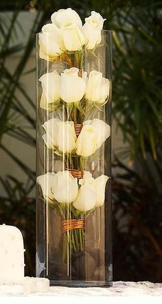 White roses of different lengths, bound in several places along the stems, and placed inside cylindrical vases