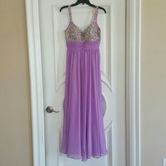 """Gorgeous crystal lavendar flowy prom dress sz4 Beautiful dress. Worn only once, in pristine condition. Sweetheart neckline, V-back. Crystals all over bust, straps and back area. Empire waistline, flowy chiffon material. Victorias secret fabulous bra size 32 C (worth over $40) was sewn in bust area for worry-free wear but can be easily removed. Gown was hemmed a little bit. I'm 5'1"""" and wore it with 4 inch heels. Size 4, fully lined. Minor stains on the bottom part of dress. I will dry clean…"""