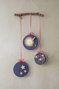 Decoração de Natal Amarre umas fitinhas no bastidor e pendure-os em um mesmo galho de árvore, com alturas diferentes.