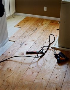 thin plywood cut into strips nailed down for a farmhouse style floor – stain or paint @ DIY Home