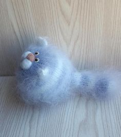 Fluffy knitted cat. Gray with white stripes. Dry felting made