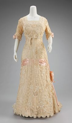 """Afternoon Dress: ca. 1908-1910, French (probably), cotton, silk. """"Irish crochet lace was very popular in the Belle Époque not only for trim but also for full garments such as this one. Its three-dimensionality gives a particularly interesting textural effect. This example employs not only three-dimensional floral motifs but actual pendant flowers that move with the wearer."""""""