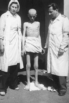 Shortly after liberation, an emaciated concentration camp inmate stands between two members of the International Red Cross. Theresienstadt, Czechoslovakia, May 1945.