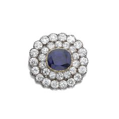 Sapphire and diamond brooch, 1900 Centring on a cushion-shaped sapphire in a cut-down collet, embellished with two rows of circular-cut diamonds, mounted in yellow gold and silver.