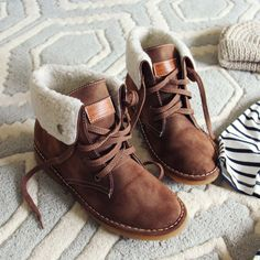 Soft chestnut tones pair with a cozy sherpa lining on these darling booties. Designed with a lace-up front, cozy flap-over sherpa top, and sweet stitch…