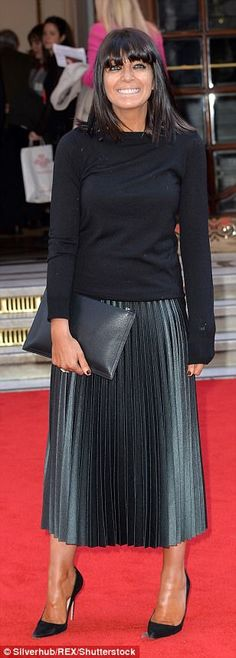 Demure: Claudia Winkleman sported a pleated grey and black skirt teamed with black sweater...