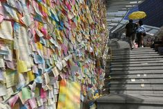 """HONGKONG-CHINA/ Thousands of colourful notes are displayed on """"Lennon Wall"""" as a couple carrying a yellow umbrella, a symbol of the Occupy Central civil disobedience movement, walks past at the Admiralty protest site in Hong Kong November 17, 2014. Police will take action this week to clear protesters from some occupied sites, according to South China Morning Post on Monday. Protesters have occupied key areas of Hong Kong for more than six weeks, camping out in some of the world's most…"""
