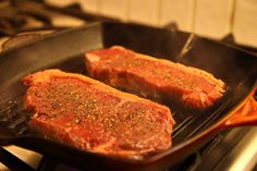 Seasoned steak cooking on the griddle.