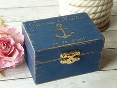 Ring Beare Box Nautical Wedding Ring Box Ring Holder Anchor Ring Box Navy Wedding Box Seashell Ring Pillow Beach Wedding Engagement Ring Box.    Rustic Beach look. Perfect for rustic beach, nautical or navy weddings.     MATERIAL and DECORATION: Wooden box painted in navy blue and distressed (or in the color you select). Engraved on the lid with an anchor, names and date.    Inside: a seashell and burlap rolls  to hold  your rings.     COLOR: You can choose your favorite color from the list…