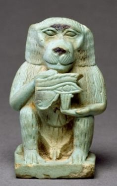 A baboon, identified with the ancient Egyptian god Thoth, holding an Eye of Horus symbol