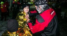 Greek volunteer Michail helping refugee child