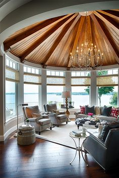 Fabulous round sunroom in a lake house decorated by Studio M Interiors