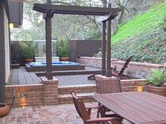 Though not particularly fond of the actual design I do like the way the brick surrounds the wood decking.  Could be the arbor that's bugging me. Outdoor Getaway - Dream Decks and Patios on HGTV