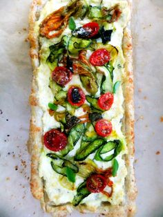 Zucchini Tart Delicate zucchini blossoms and thin ribbons of squash pressed into cheesey flavored ricotta highlight this summer bounty tart and it's nothing short of perfection!