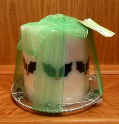 Holly-themed pillar candle with glass dish