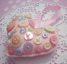 Would be fun for baby to play with. Pink heart decoration  This plump pink heart is cut and stitched by hand from soft wool mix felt and then smothered in the most gorgeous pastel coloured buttons of various shapes and sizes. Stuffed with polyester toy filling and finished with baby pink polka dot grosgrain ribbon, it makes a fitting addition to any shabby chic interior.
