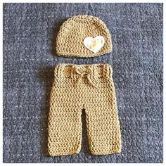 Crochet neutral Valentines Day Inspired Newborn Baby Outfit. This sweet set is Size newborn. This set includes: - A tan hat with a white felt & fabric heart stitched onto the hat. The fabric is white & metallic gold. - A pair of tan pants with a draw string. The pants have the same
