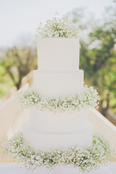 white 4 tier wedding cake decorated with gypsophila / http://www.himisspuff.com/simple-elegant-all-white-wedding-color-ideas/9/