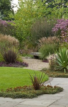 ⓒ Acres Wild. Enclosure from backdrop of deciduous trees, layered forward with ornamental grasses and Eupatorium. Ground covers and pea gravel at low, stone seating area.