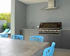"This backyard kitchen proves valuable in the summer months, when most of the entertaining is done by the pool. Claire says, ""We designed our al fresco to get the sea breeze and still be protected. I love the outdoor table. It's made of concrete fiberglass compound, and I've never seen anything else like it."""