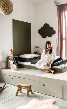 Lit surélevé sur une estrades avec des rangements intégrés. - Stands on a raised bed with integrated storage.
