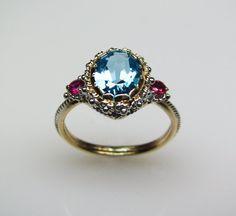 ONTWERPDETAILS: De Blue Topaz & Ruby Ring is volledig handgemaakt van gerecycled 14K geel en witgoud. Het beschikt over een 9X7mm blauwe topaas als haar grootste steen, ingelijst in een filigraan ingericht bezel instelling. Aan elke kant van deze glinsterende blue topaz is een 5pt conflict vrije ruby (10pts in totaal).  GROOTTE: Een toeslag geldt voor maten groter dan 7 1/2, zie grootte voor het tarief details.  AANPASSING: Dit ontwerp is ook beschikbaar met verschillende edelstenen ook in…