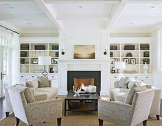 The family room offers perfect symmetry from the seating to the perfectly-styled built-ins. On the left is the Quatrefoil Floor Lamp by Suzanne Kasler for Visual Comfort & Co. (shown in Aged Iron) while a pair of the Vendome Single Sconces by Thomas O'Brien for Visual Comfort & Co. (shown in Bronze) flank the fireplace.