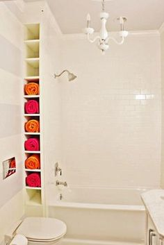 Shelf for towels, on the wall, by the tub. Small bathroom organization. I think it would be cool to paint the inside of the shelf lime green with pink towels. - My-House-My-Home