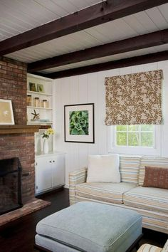 Living room in the Hamptons with striped sofa, brick fireplace and leaf print Roman shades ?marquis redo