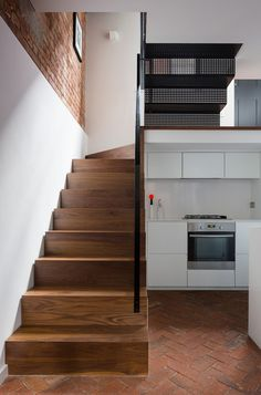 The industrial walnut stairs leading to the ground floor transition into perforated steel stairs at the top to allow natural light from the landing window into the basement. Townhouse Interior, London Townhouse, Interior Stairs, Rustic Staircase, Modern Staircase, Staircase Design, Steel Stairs, Wood Stairs, Traditional Staircase