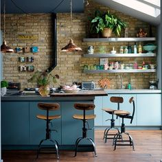 Industrial, modern & eclectic. Vintage stools, exposed brick, stainless steel shelves & copper pendants.