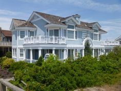 Beautiful beach house...I love the arch and the railing around the second floor deck.