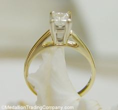 Princess High Mount Cathedral Solitaire Diamond Engagement Ring -- $379.95 MedallionTradingCompany.com The solitaire is set in a high mount cathedral setting that sits 7.7mm off the finger, giving the diamond a larger look   Markings: 14k, makers mark and 3/8 (carat size) is marked on the inside which confirms the total weight of the diamond  Ring Size: 5 resizeable  Total Weight: 2.7 grams  Diamond:  1 Princess cut natural, un-enhanced diamond solitaire, measures 4.71mm  long by 3.9mm wide…