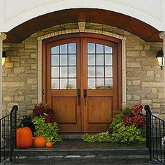 These arched-top, solid mahogany doors are just as earthy and appealing as the autumn harvest display gracing the entryway. The doors are the perfect complement to the stonework of the facade and bead board of the porch ceiling. Custom Exterior Doors, Interior And Exterior, Interior Design, Iron Front Door, Front Entry, Porch Ceiling, Front Door Design, Entrance Doors, Barn Doors